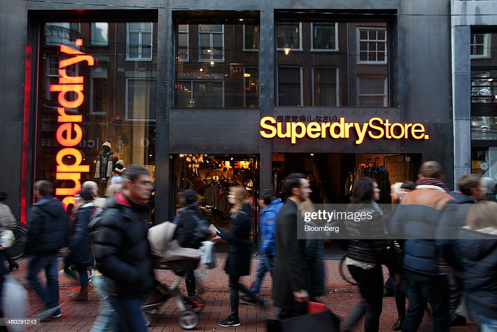Pedestrians pass a Superdry clothing fashion store, operated by SuperGroup Plc, in Amsterdam, Netherlands, on Thursday, Jan. 2, 2014. The Netherlands will grow by 0.5 percent in 2014 as the world economy improves and consumer confidence picks up, the country's central bank forecast Dec. 9. Photographer: Jasper Juinen/Bloomberg via Getty Images