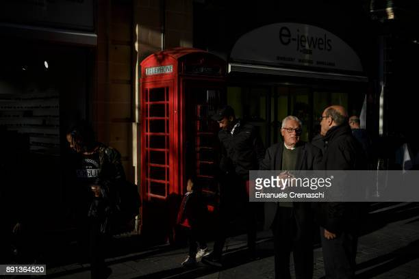 Pedestrians pass a traditional British red telephone box in Trik IrRepubblika on December 7 2017 in Valletta Malta Valletta a fortified town that...