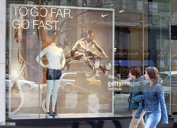 Pedestrians pass a window ad of athlete Marion Jones promoting Nike's 'Air Vapor Control' shoe at a Niketown store March 19 2004 in Chicago illinois...