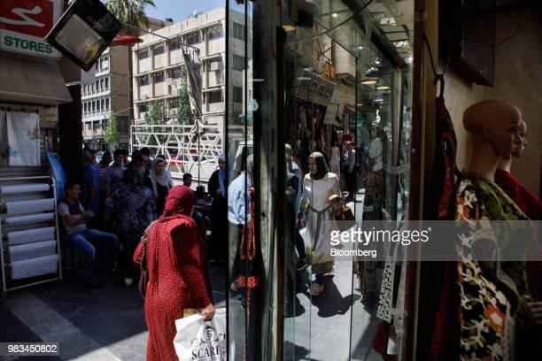Pedestrians pass a women's fashion store in Amman Jordan on Thursday June 21 2018 President Trump and First Lady Melania Trump will host JordansKing...
