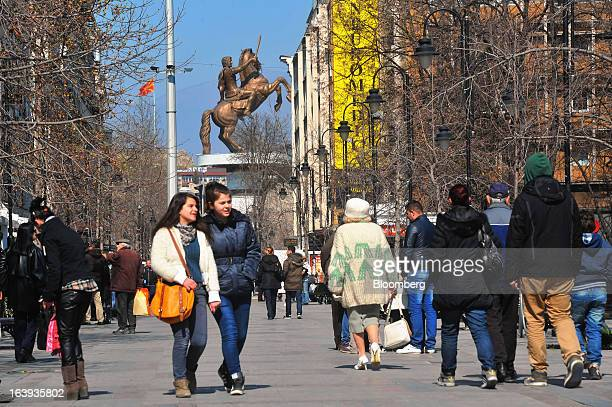 Pedestrians pass along a shopping street near a statue of Alexander the Great in central Skopje Macedonia on Sunday March 17 2013 Macedonia's economy...