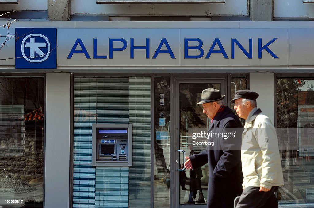 Pedestrians pass an Alpha Bank AE branch in central Skopje, Macedonia, on Sunday, March 17, 2013. Macedonia's economy contracted by a real 0.3% on the year in 2012, compared to a growth of 2.8% a year earlier, an estimate released by the country's statistics office showed. Photographer: Oliver Bunic/Bloomberg via Getty Images