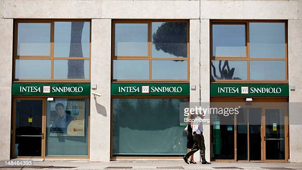 Pedestrians pass an Intesa Sanpaolo SpA bank branch in Rome, Italy, on Tuesday, July 17, 2012. UniCredit SpA and Intesa Sanpaolo SpA were among 13...