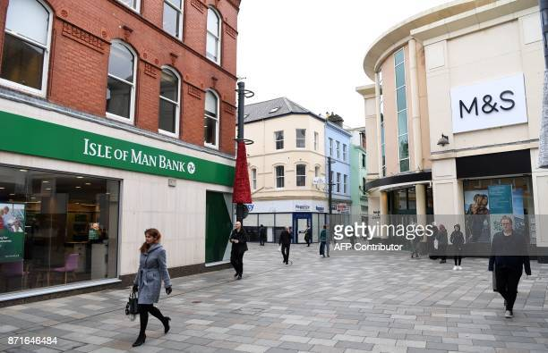 Pedestrians pass an Isle of Man Bank and a Marks and Spencer store in Douglas on the Isle of Man an island in the Irish Sea off of the west coast...