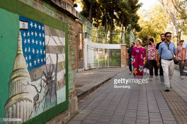 Pedestrians pass antiAmerican wall murals beside the entrance to the former US embassy in Tehran Iran on Sunday Aug 5 2018 Irans central bank acting...