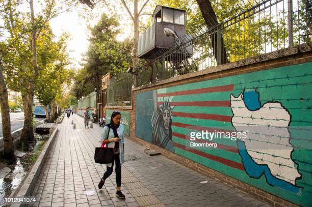 Pedestrians pass antiAmerican wall murals on the wall of the former US embassy in Tehran Iran on Sunday Aug 5 2018 Irans central bank acting on the...