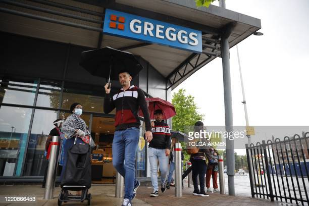 Pedestrians pass as customers queue to enter a reopened Greggs bakery in London on June 18, 2020 after the chain reopened hundreds of stores around...