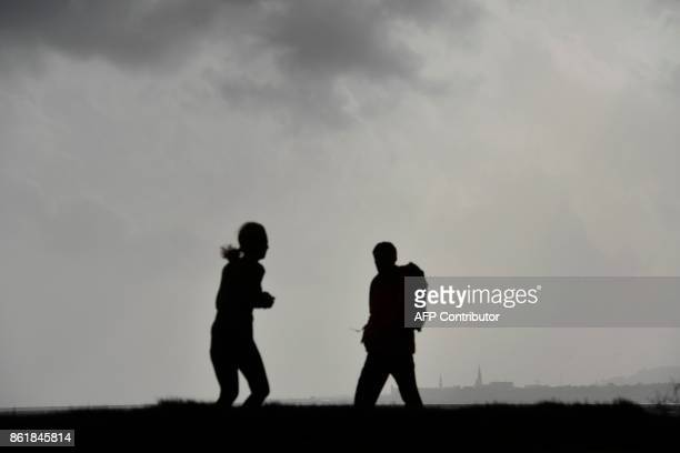 Pedestrians pass as dark clouds gather at Dublin Bay on October 16 2017 as Ireland braces for the passing of the storm Ophelia Schools were closed on...