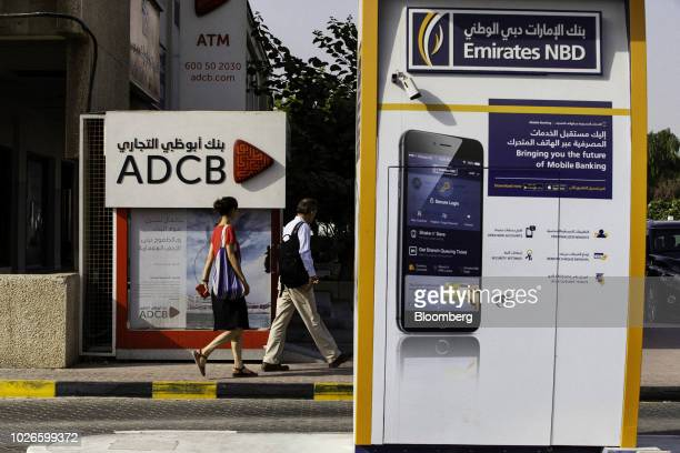 Pedestrians pass automated teller machines operated by Emirates NBD PJSC and Abu Dhabi Commercial Bank PJSC banks in Dubai United Arab Emirates on...