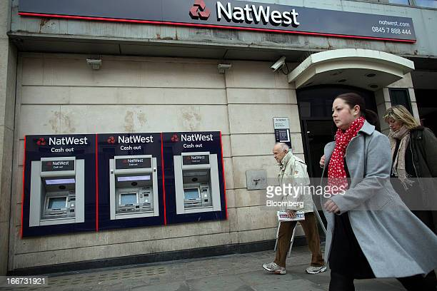 Pedestrians pass automated teller machines outside a NatWest bank branch part of the Royal Bank of Scotland Group Plc in London UK on Tuesday April...