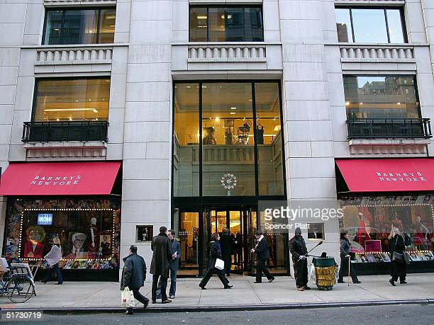 Pedestrians pass Barneys New York November 11 2004 in New York City The Jones Apparel Group has announced a deal to buy Barneys the clothing chain...