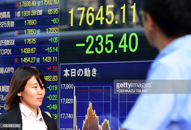 Pedestrians pass before a share prices board in Tokyo on September 28 2015 Tokyo shares closed 132 percent lower on September 28 as the yen...