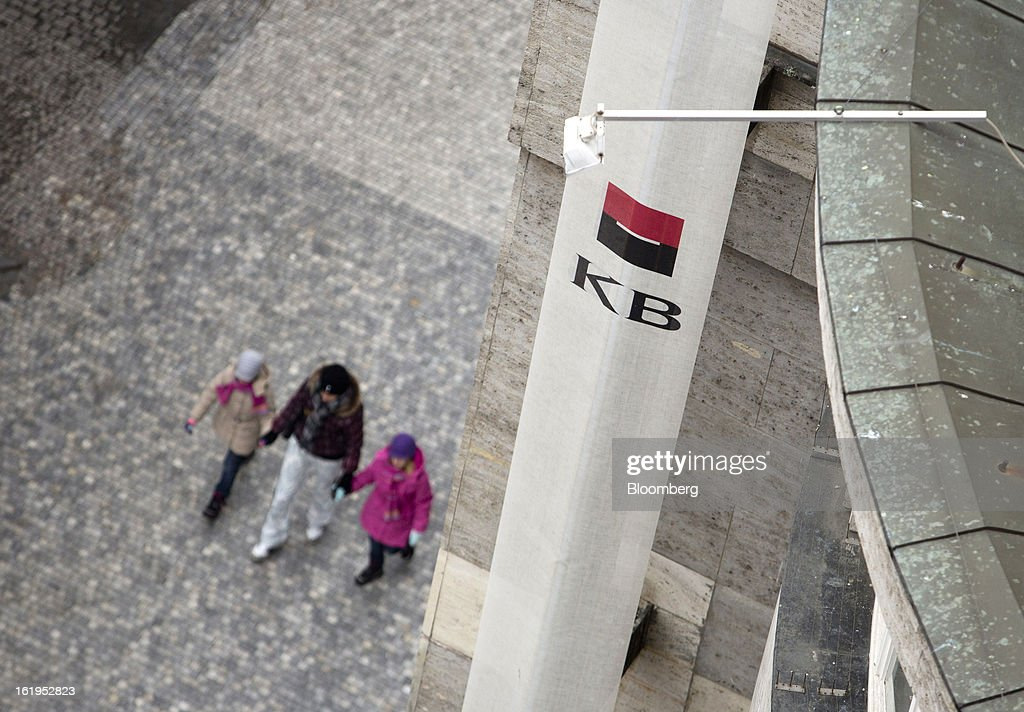 Pedestrians pass beneath a Komercni Banka AS logo outside a branch in Prague, Czech Republic, on Sunday, Feb. 17, 2013. Worsened outlook for Czech economy is in line with the government's expectations and lower-than-planned tax revenue is 'manageable' under 2013 budget, Prime Minister Petr Necas said on Czech public television. Photographer: Martin Divisek/Bloomberg via Getty Images