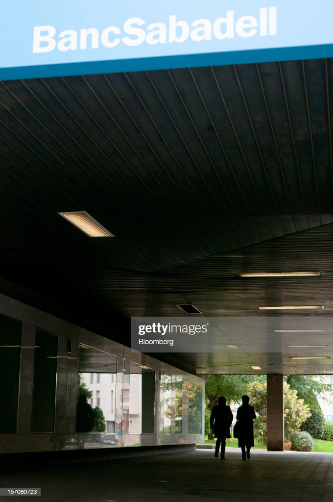 Pedestrians pass beneath a logo outside offices of Banco Sabadell SA in Sabadell, Spain, on Wednesday, Nov. 28, 2012. Spanish banks getting European aid will shrink their balance sheets more than 60 percent, the European Commission said, as BFA-Bankia, the biggest rescued lender, expects to lose 19 billion euros ($25 billion) this year. Photographer: Stefano Buonamici/Bloomberg via Getty Images