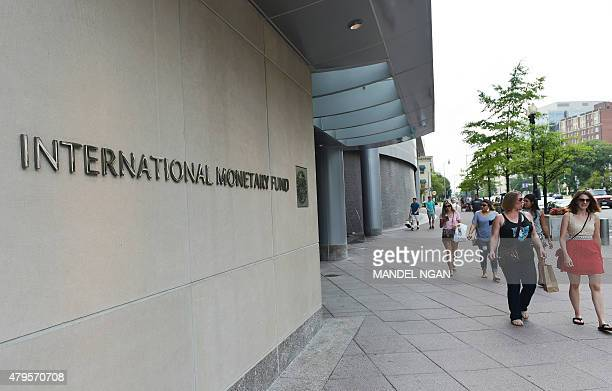Pedestrians pass by a headquarters building of the International Monetary Fund in Washington DC on July 5 2015 The euro was dropping against the...