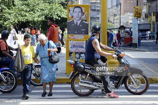 Pedestrians pass by a picture of late Venezuelan former President Hugo Chavez in Caracas on August 23 2013 Nearly six month of his death the image of...