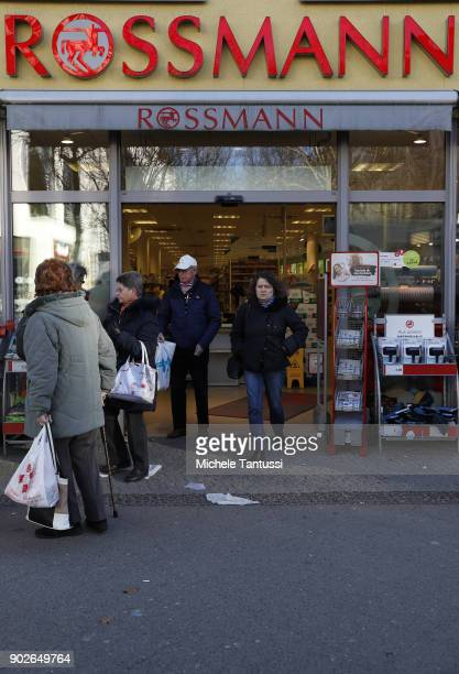 Pedestrians pass by a Rossmann Drogerie shop on January 8 2018 in Berlin Germany According to government statisticians nominal revenue grew compared...