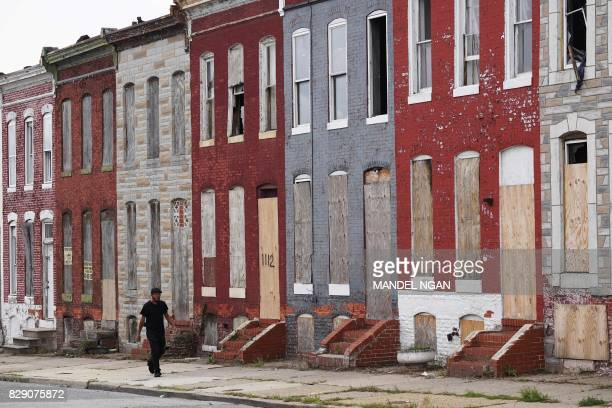 Pedestrians pass by a row of boarded up houses in east Baltimore on August 8 2017 Baltimore a city of 28 million is troubled by drug use poverty and...