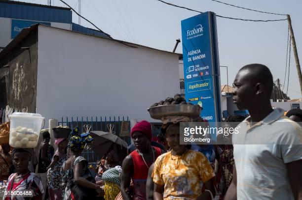 Pedestrians pass by an Ecobank Guinea Bissau bank branch at Bandim market in Bissau GuineaBissau on Monday Feb 12 2018 The International Monetary...