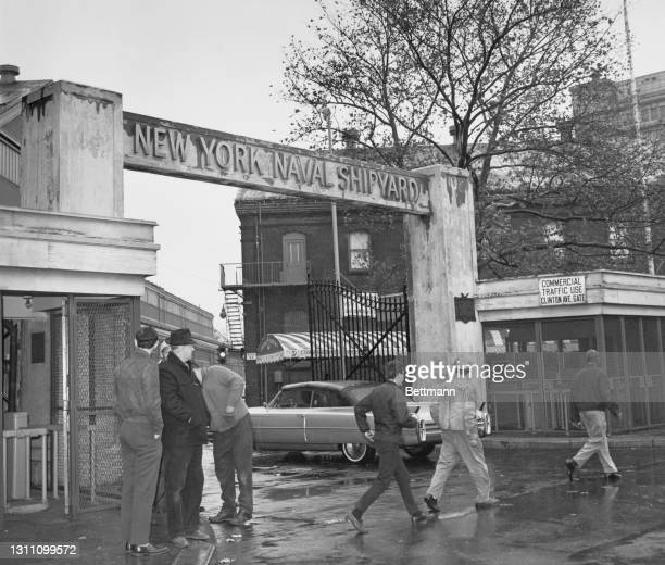 Pedestrians pass by as a car drives through the main entrance of the 'New York Naval Shipyard', also known as Brooklyn Navy Yard, on the day the...
