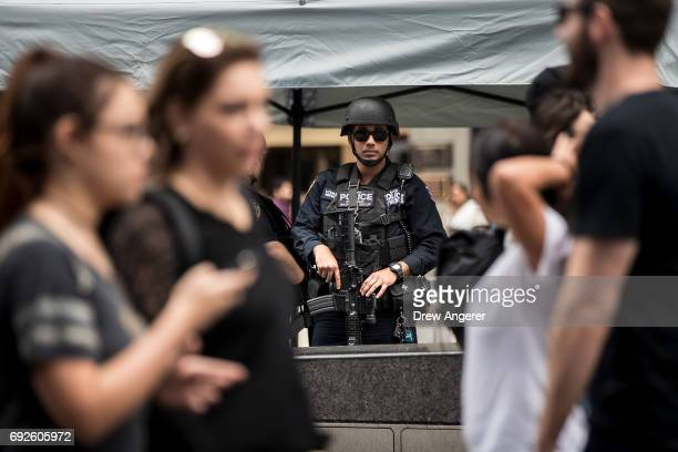 Pedestrians pass by as a member of the New York City Police Department's counterterrorism squad stand guard in Times Square June 5 2017 in New York...