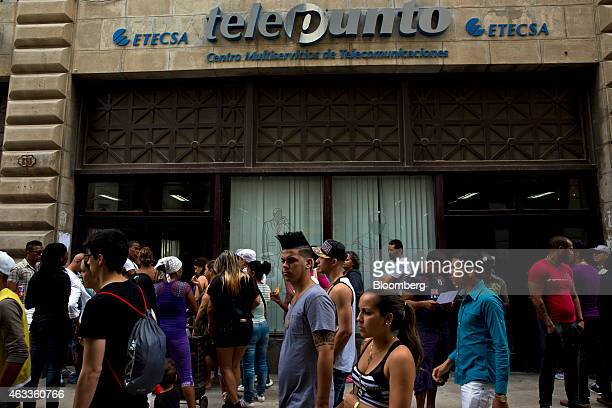 Pedestrians pass by people waiting in line at an Empresa de Telecomunicaciones de Cuba SA office the staterun telecom company in Havana Cuba on...