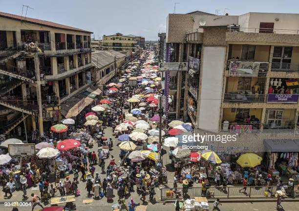 Pedestrians pass by stalls at Makola market in Accra Ghana on Thursday March 15 2018 Ghana wants to shake up the way it collects tax with the...