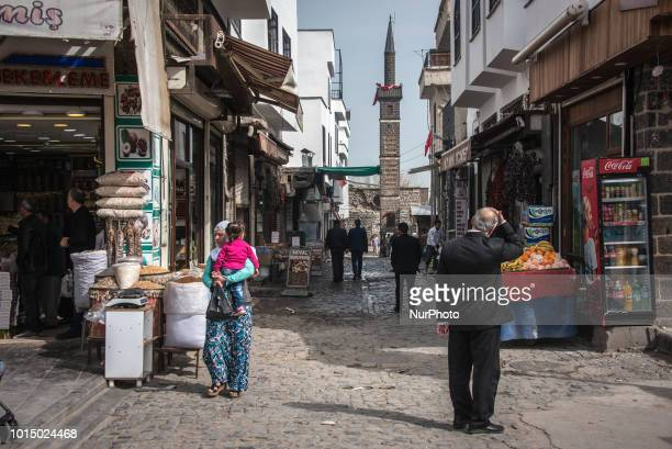 Pedestrians pass by the historic Sheikh Matar Mosque and it's four-legged minaret, which was damaged during military operations in the Sur district...