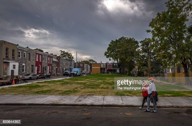 Pedestrians pass by where the houses in the 900 block of NBradford street once stood now a lawn of newly seeded grass on September 2016 in Baltimore...