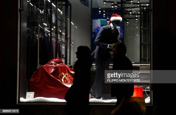 Pedestrians pass Christmas themed department store window displays as they walk in central Rome on December 9 as the first weekend of Christmas...