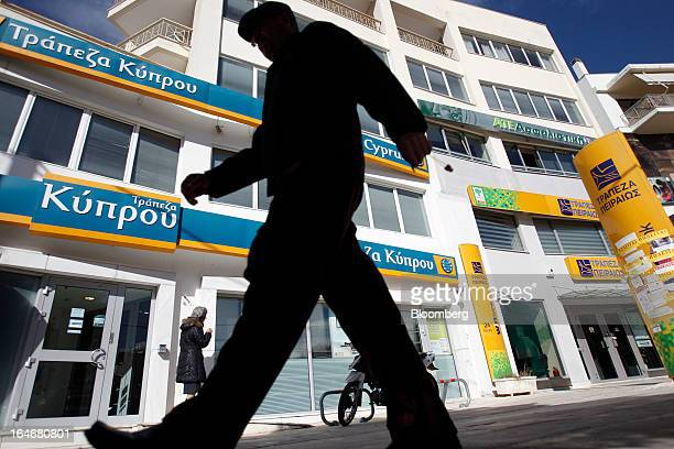 Pedestrians pass closed branches of Piraeus Bank SA right and Bank of Cyprus Plc left in Athens Greece on Tuesday March 26 2013 Piraeus Bank SA...