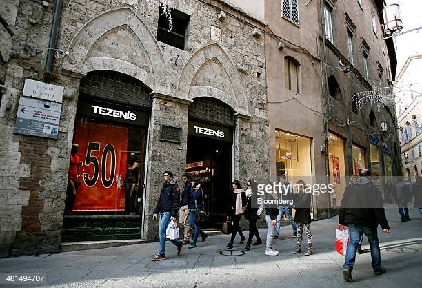 Pedestrians pass clothes stores advertising sales in their window displays in Siena Italy on Wednesday Jan 8 2014 Banca Monte dei Paschi di Siena SpA...