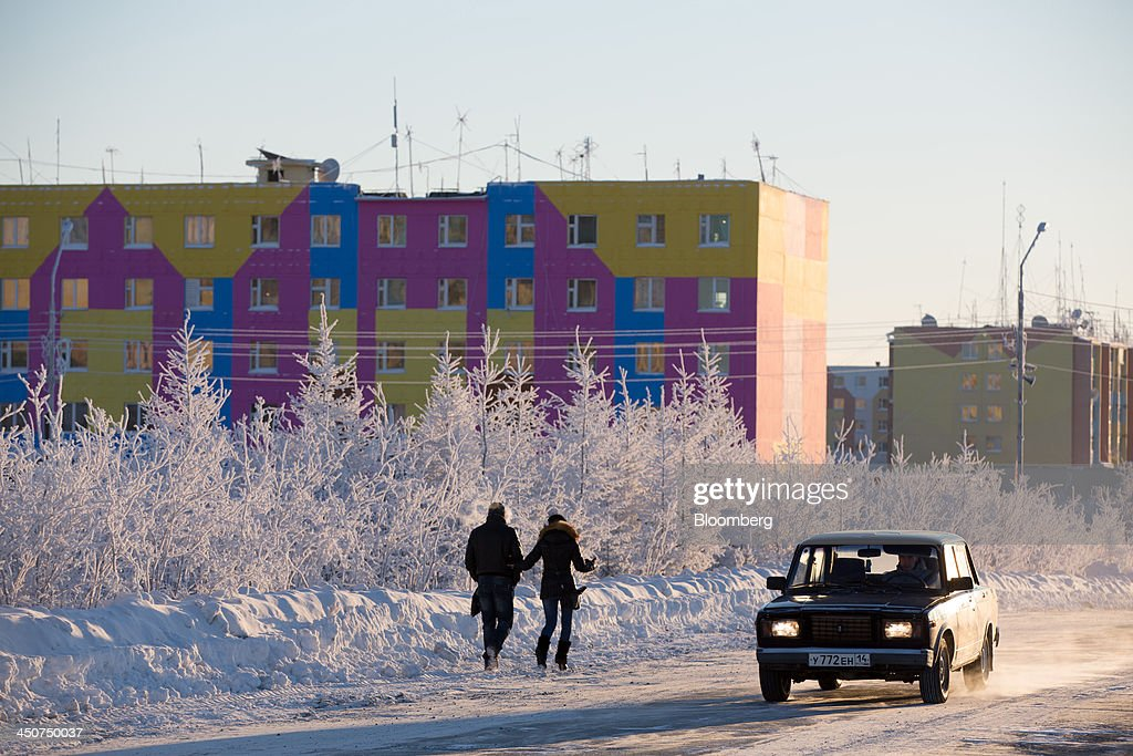 Pedestrians pass frozen trees covered with hoar frost during a period of extreme cold in Udachny, Russia, on Sunday, Nov. 17, 2013. OAO Alrosa, the world's largest diamond producer, raised about $1.3 billion in an oversubscribed share sale from investors including Oppenheimer Funds Inc. and Lazard Ltd.'s asset-management unit, First Deputy Prime Minister Igor Shuvalov said. Photographer: Andrey Rudakov/Bloomberg via Getty Images