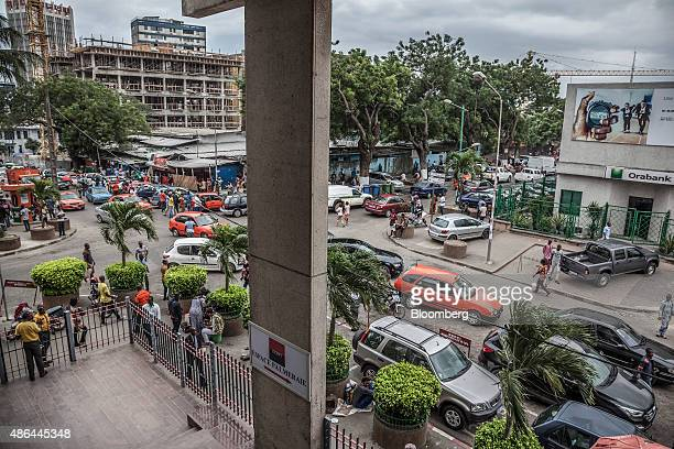 Pedestrians pass heavy road traffic outside an Orabank bank branch, right, in the financial district of Abidjan, Ivory Coast, on Monday, Aug. 31,...