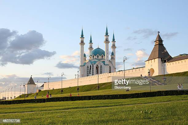 Pedestrians pass historical defensive walls outside the Kul Sharif mosque in Kazan Russia on Tuesday July 21 2015 Russia's central bank halted...