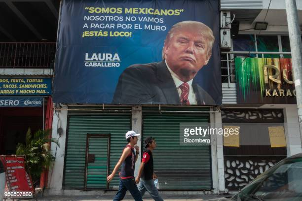 """Pedestrians pass in front a sign with an image of U.S President Donald Trump that reads """"We Are Mexican. We Are Not Going To Pay For A Wall. You Are..."""