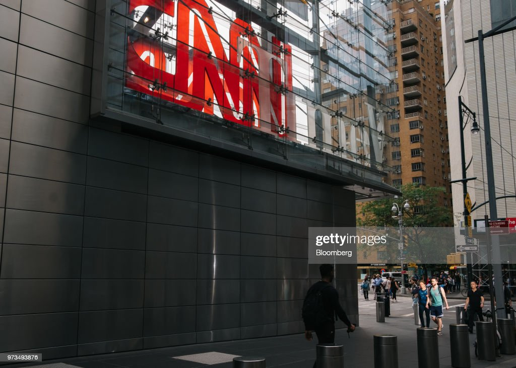 Pedestrians pass in front of a building complex displaying Time Warner Inc. brand CNN television network signage in New York, U.S., on Wednesday, June 13, 2018. AT&T Inc.'s sweeping court victory allowing its takeover of Time Warner Inc. delivers a sharp setback to the Justice Department's new approach to policing mergers under President Donald Trump and promises to spark a merger wave across industries. Photographer: Christopher Lee/Bloomberg via Getty Images