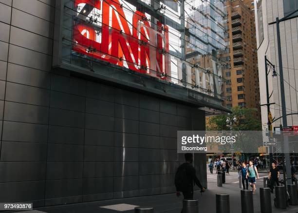 Pedestrians pass in front of a building complex displaying Time Warner Inc brand CNN television network signage in New York US on Wednesday June 13...