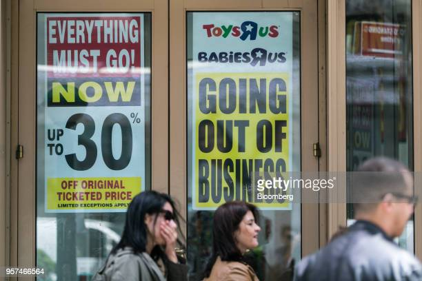 Pedestrians pass in front of a Going Out Of Business sign displayed outside a Toys 'R' Us retail store at Times Square in New York US on Friday May...