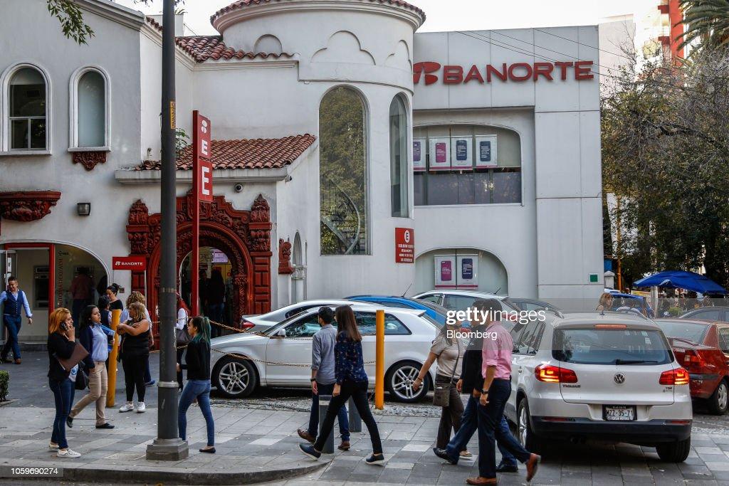 Pedestrians pass in front of a Grupo Financiero Banorte SAB bank