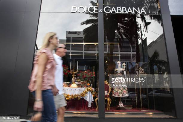 Pedestrians pass in front of a holiday window display at the Dolce Gabbana Srl store on Rodeo Drive in Beverly Hills California US on Saturday Dec 9...