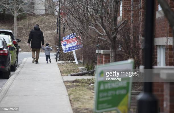 Pedestrians pass in front of a home for sale in the Le Plateau MontRoyal borough of Montreal Quebec Canada on Saturday April 14 2018 An economic...