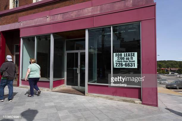 """Pedestrians pass in front of a real estate sign that reads """"For Lease"""" outside an empty storefront in downtown Concord, New Hampshire, U.S., on..."""