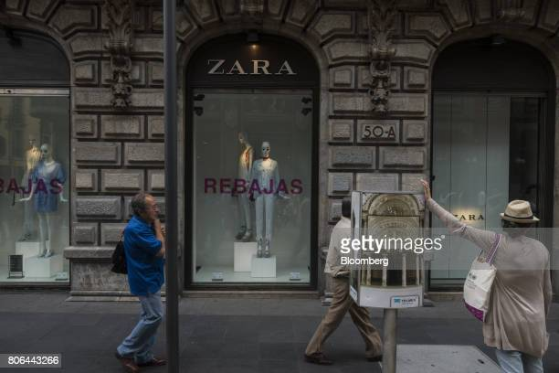 Pedestrians pass in front of a sale sign displayed in the window of a Zara store operated by Inditex SA on Francisco I Madero Avenue in Mexico City...