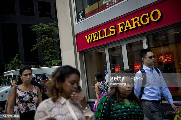 Pedestrians pass in front of a Wells Fargo Co bank branch in New York US on Tuesday July 12 2016 Wells Fargo Co is scheduled to release earnings...