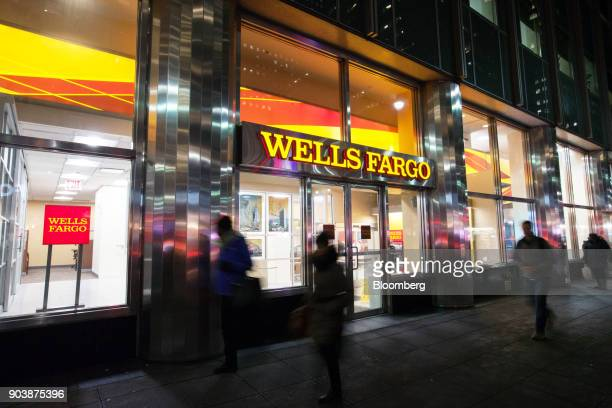 Pedestrians pass in front of a Wells Fargo Co bank branch in New York US on Tuesday Jan 9 2018 Wells Fargo Co is scheduled to release earnings...