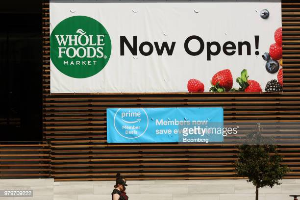 A sign advertising special deals for Amazoncom Inc Prime members stands outside of a Whole Foods Market Inc location during the grand opening in...