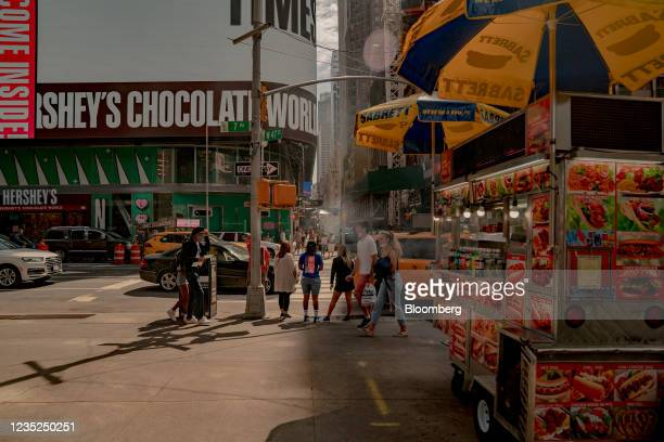 Pedestrians pass in front of food carts in the Times Square neighborhood of New York, U.S., on Saturday, Sept. 4, 2021. This month, as Broadway...