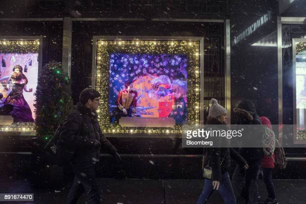 Pedestrians pass in front of holiday window displays at Bloomingdale's Inc department store in New York US on Saturday Dec 9 2017 Bloomberg is...