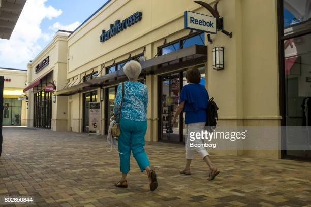 Pedestrians pass in front of Reebok International Ltd signage and a Charlotte Russe Inc store at the Palm Beach Mall Holdings LLC Outlets in West...